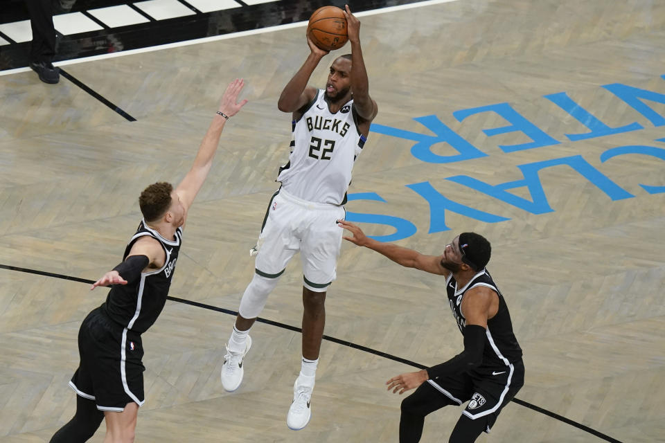 Milwaukee Bucks' Khris Middleton (22) shoots over Brooklyn Nets' Blake Griffin, left, and Bruce Brown, right, during overtime of Game 7 of a second-round NBA basketball playoff series Saturday, June 19, 2021, in New York. (AP Photo/Frank Franklin II)