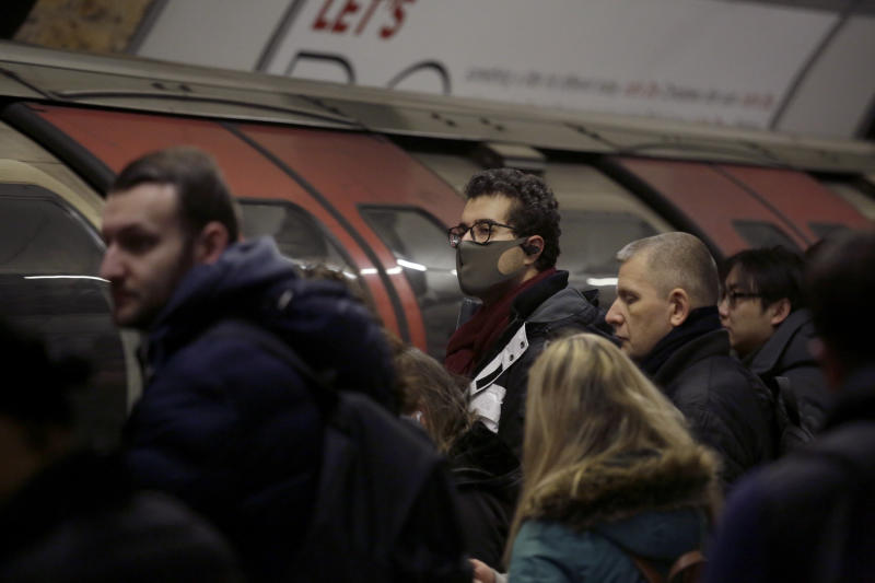 A man wearing a face mask waits to board an underground train on the Central Line at Bank station in London, Wednesday, March 4, 2020. British authorities laid out plans Tuesday to confront a COVID-19 epidemic, saying that the new coronavirus could spread within weeks from a few dozen confirmed cases to millions of infections, with thousands of people in the U.K. at risk of death. (AP Photo/Matt Dunham)