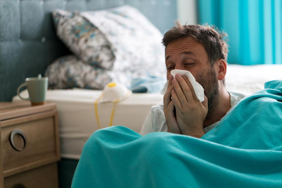 Sick man with covid-19 symptoms in bed