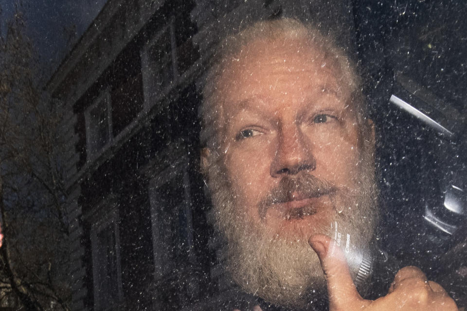 Julian Assange gestures as he arrives at Westminster Magistrates' Court in London, after the WikiLeaks founder was arrested by officers from the Metropolitan Police and taken into custody Thursday April 11, 2019. Police in London arrested WikiLeaks founder Assange at the Ecuadorean embassy Thursday for failing to surrender to the court in 2012, shortly after the South American nation revoked his asylum .(Victoria Jones/PA via AP)