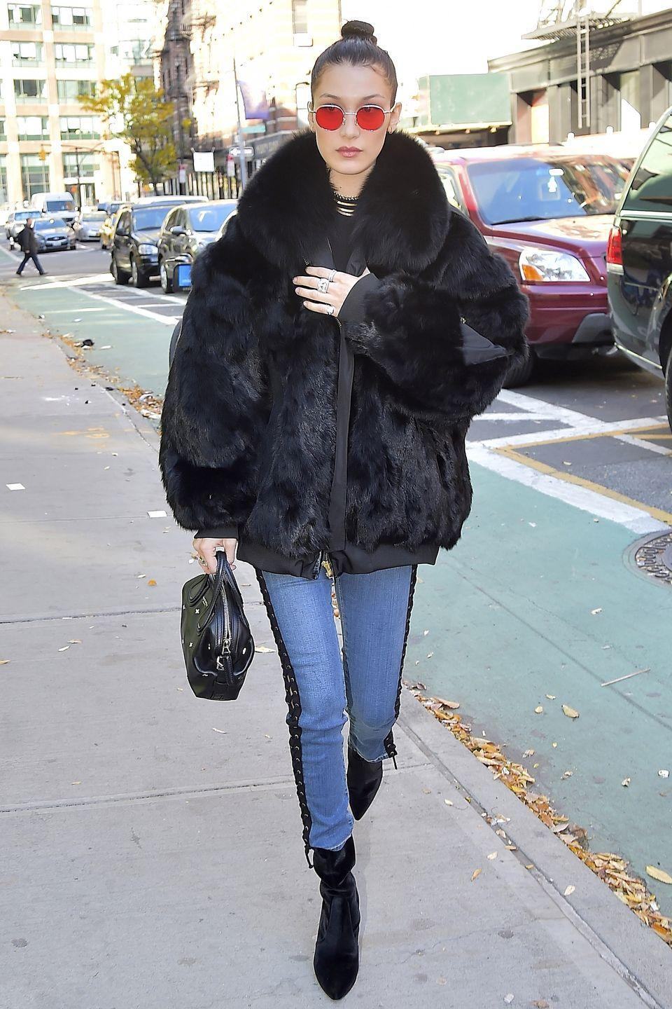 <p>Bella bundles up in a fur coat, light wash lace-up skinny jeans, velvet pointed-toe booties, a black handbag, red-tinted sunglasses, flashy silver rings and layered gold necklaces while out in NYC. </p>