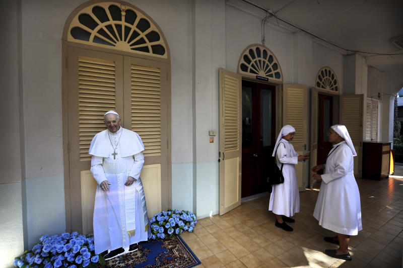 Nuns talk near the life-size poster of Pope Francis at a convent near the Assumption Cathedral in Bangkok, Thailand, Wednesday, Nov. 20, 2019. Pope Francis is heading to Thailand to encourage members of a minority Catholic community in a Buddhist nation and highlight his admiration for their missionary ancestors who brought the faith centuries ago and endured persecution. (AP Photo/Manish Swarup)
