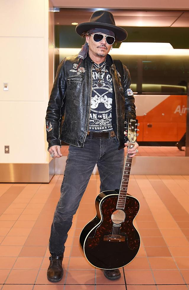 <p>Depp rock 'n' rolled into Tokyo's Haneda Airport looking cool. (He left the pirate gear at home.) (Photo: Jun Sato/GC Images) </p>
