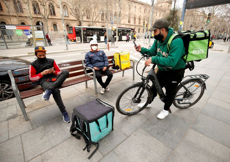 FILE PHOTO: Delivery riders with backpacks of Glovo, Uber eats and Deliveroo wait for orders at Universitat square in Barcelona