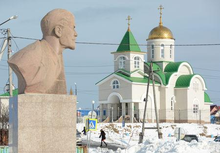 FILE PHOTO: A bust of Soviet state founder Vladimir Lenin is seen in front of a Russian Orthodox church in Yuzhno-Kurilsk on the Island of Kunashir, one of four islands known as the Southern Kurils in Russia and the Northern Territories in Japan, December 21, 2016. REUTERS/Yuri Maltsev/File Photo