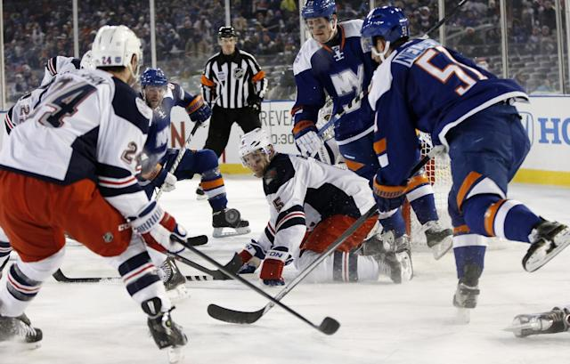 New York Rangers defenseman Dan Girardi (5) defends as New York Islanders center Frans Nielsen (51) takes a shot in the waning seconds an NHL hockey game at Yankee Stadium in New York, Wednesday, Jan. 29, 2014. The Rangers defeated the Islanders 2-1. (AP Photo/Kathy Willens)
