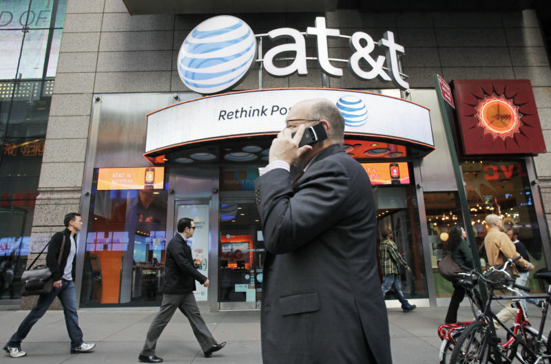 FILE - In this Oct. 18, 2011 file photo, a man using a cell phone passes an AT&T store, in New York.   AT&T is gaining new wireless subscribers at the lowest rate in eight years, as the number of people joining the network through resellers and non-phone devices like the Kindle is dropping sharply. (AP Photo/Mark Lennihan)