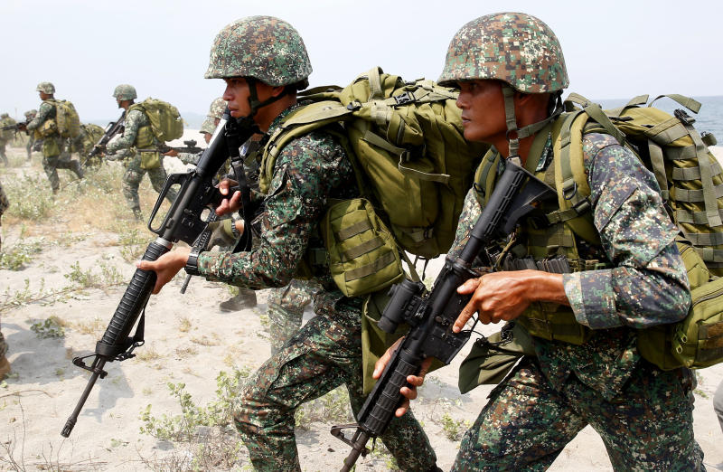 """FILE - In this May 9, 2018, file photo, Philippine and U.S. Marines begin their assault after storming the beach during an amphibious landing exercise during the two-week joint U.S.-Philippines military exercise facing the South China Sea in the northwestern Philippines. More than 2,000 U.S. and Philippine military personnel, along with a small contingent of Japanese forces, are holding annual combat exercises aimed at responding rapidly to crises and natural disasters and underscoring their commitment to keeping the region """"free and open."""" (AP Photo/Bullit Marquez, File)"""