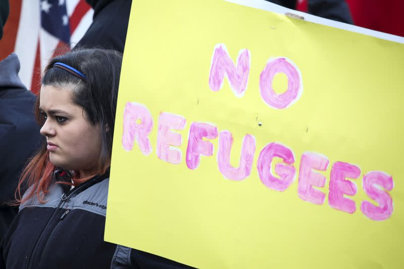 FILE PHOTO: A protestor holds an anti-refugee sign to protest the United States' acceptance of Syrian refugees at the Washington State capitol in Olympia