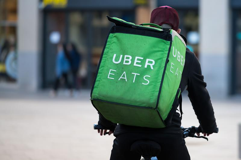 A Uber Eats worker rides a bike through the city centre in Cardiff, United Kingdom.