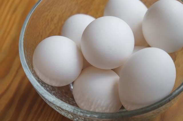 A small bowl filled with eggs on a hardwood counter.