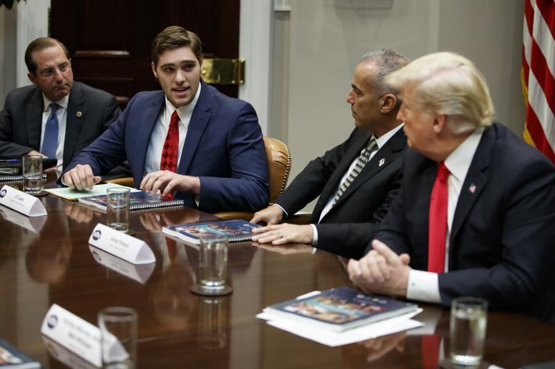 FILE - In this Dec. 18, 2018 file photo, JT Lewis, brother of Sandy Hook victim Jesse Lewis, speaks to President Donald Trump during a roundtable discussion on the Federal Commission on School Safety report, in the Roosevelt Room of the White House in Washington. From left, Secretary of Health and Human Services Alex Azar, Lewis, Andy Pollack, father of Parkland victim Meadow Pollack, and Trump. Lewis lost his 6-year-old brother, Jesse, in the 2012 Sandy Hook Elementary School shooting. He now is a University of Connecticut student and is running for the 2020 state Senate as a Republican, calling for better school security and mental health programs. (AP Photo/Evan Vucci, File)