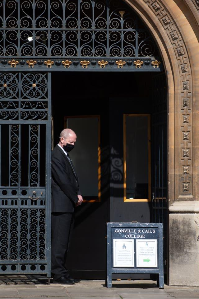 A porter observes a minute's silence at a college in Cambridge