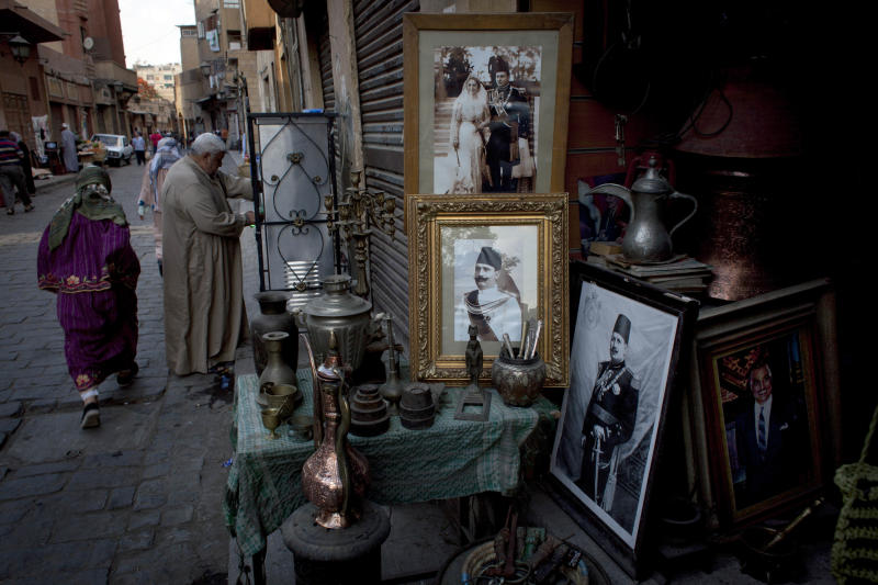 In this photo taken Sunday, May 12, 2013, an antique shop displays photos of late Egyptian leaders, on El-Moez Street of the historical Fatimid Cairo, Egypt. Cairo, the Arab world's most populated city, is often referred to as an open-air museum of Islamic antiquities and the city of 1,000 minarets. But its rich history and contributions to Islamic art has languished. (AP Photo/Nasser Nasser)
