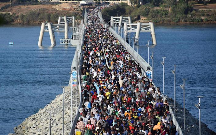 Kenyan commuters walk on the Mombasa floating bridge as ferry services are paused in commuting hours to curb the spread of Covid - Dihoff Mukoto/AFP