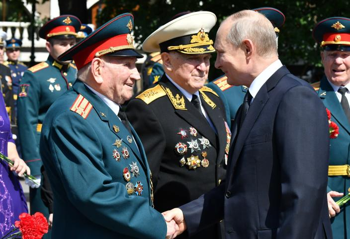 Russian President Vladimir Putin, right, greets Russian WWII veterans during a wreath laying ceremony at the Tomb of Unknown Soldier in Moscow, Russia, Tuesday, June 22, 2021, marking the 80th anniversary of the Nazi invasion of the Soviet Union. (Alexei Nikolsky, Sputnik, Kremlin Pool Photo via AP)