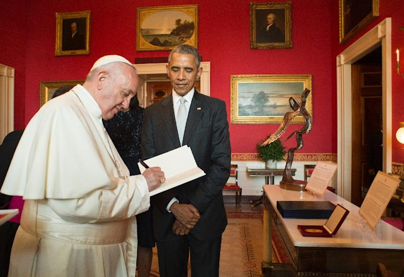 This photo released by L'Osservatore Romano shows Pope Francis with US President Barack Obama as he signs the ecological encyclical at the White House, September 23, 2015 in Washington, DC (AFP Photo/)
