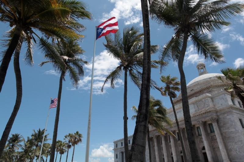 The flags of the U.S. and Puerto Rico fly outside the Capitol building in San Juan