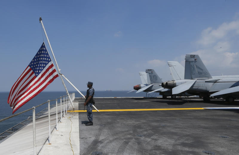 A U.S. Marine stands guard on the flight deck of the USS Carl Vinson aircraft carrier anchors off Manila, Philippines, for a five-day port call along with guided-missile destroyer USS Michael Murphy, Saturday, Feb. 17, 2018. Lt. Cmdr. Tim Hawkins told The Associated Press that American forces will continue to patrol the South China Sea wherever international law allows when asked if China's newly built islands could restrain them in the disputed waters. (AP Photo/Bullit Marquez)