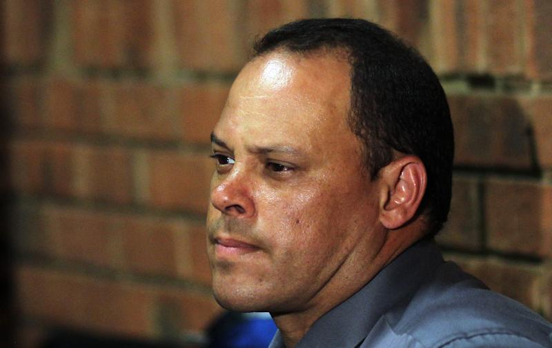 FILE- In this Wednesday, Feb. 20, 2013 file photo, Investigating officer Hilton Botha, sits inside the court witness box during the Oscar Pistorius bail hearing at the magistrate court in Pretoria, South Africa. The lead investigator in the murder case against Oscar Pistorius faces attempted murder charges himself over a 2011 shooting, police said Thursday, Feb. 21, 2013, in another potentially damaging blow to the prosecution. Prosecutors said they were unaware of the charges against veteran detective Hilton Botha when they put him on the stand in court to explain why Pistorius should not be given bail in the Valentine's Day shooting death of his girlfriend. Police Brig. Neville Malila told The Associated Press that Botha — who gave testimony in the Pistorius bail hearing on Wednesday — is scheduled to appear in court in May on seven counts of attempted murder related to an incident in October 2011 when Botha and two other police officers fired at a minibus they were trying to stop. (AP Photo/Themba Hadebe, File)