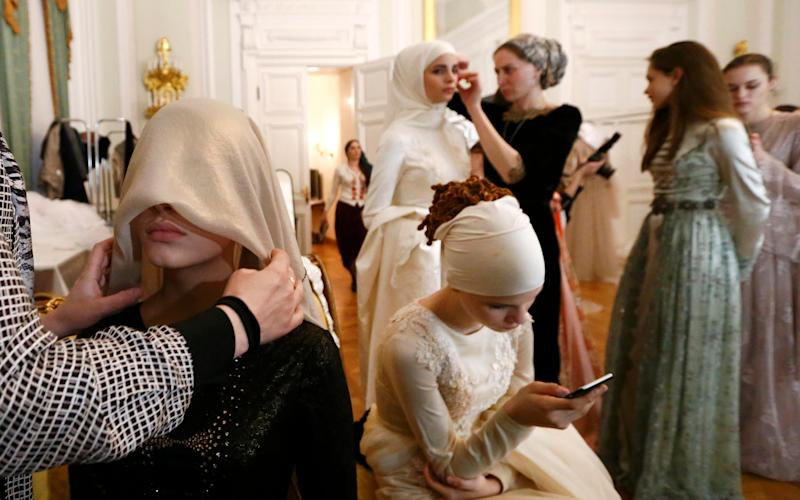 Models get assistance while preparing backstage before a show of the Firdaws fashion house led by Aishat Kadyrova - Credit: Reuters