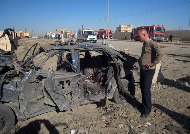 A man stands next to a destroyed vehicle at the scene of a car bomb attack in Kirkuk, 290 kilometers (180 miles) north of Baghdad, Iraq, Tuesday, March 20, 2012. Officials say attacks across Iraq have killed and wounded scores of people, police said, in a spate of violence that was dreaded in the days before Baghdad hosts the Arab world's top leaders. (AP Photo/Emad Matti)