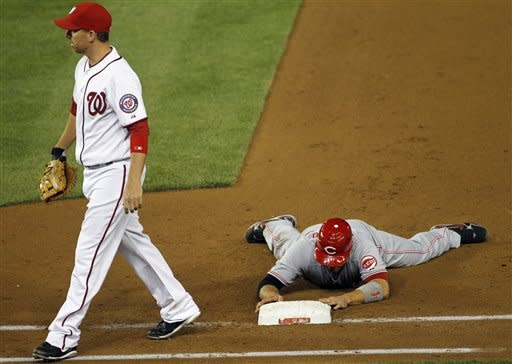 Cincinnati Reds' Joey Votto (19) lies on the ground after being called out at first base after Scott Rolen hit into a doubleplay in the sixth inning of a baseball game against the Washington Nationals, Friday, April, 13, 2012, in Washington. Walking back to the dugout is Washington Nationals' Adam LaRoche (25). (AP Photo/Pablo Martinez Monsivais)
