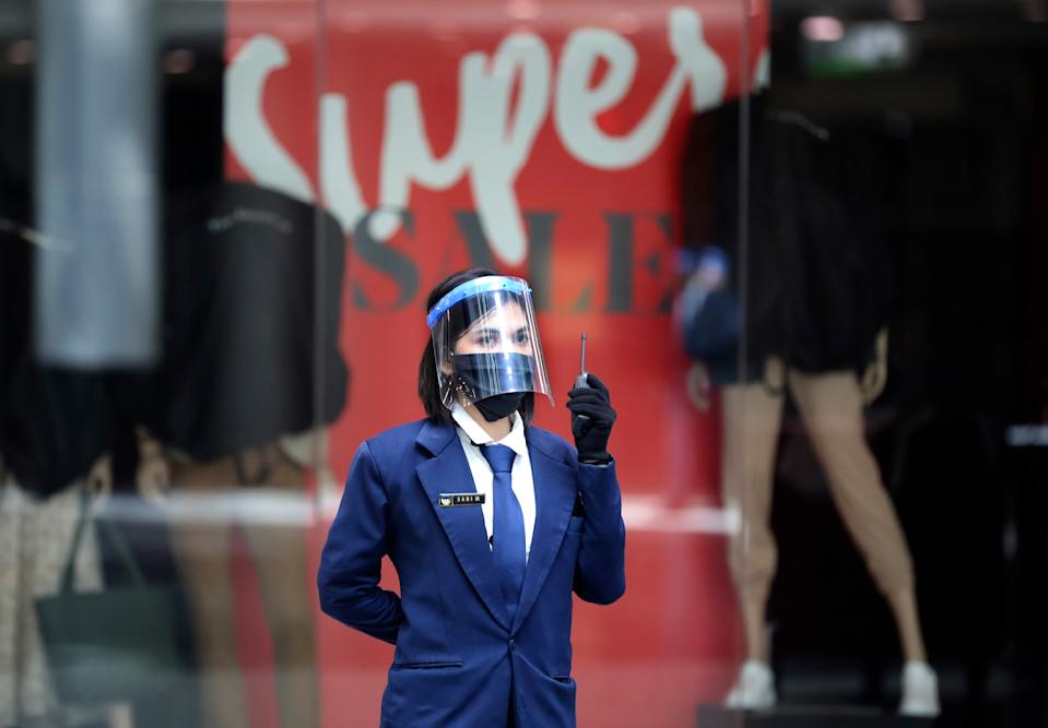 A security guard wearing a protective face shield as a precaution against coronavirus outbreak talks on her radio at Margo City shopping mall, which has been closed after a number of employees of a supermarket at the mall were tested positive for the virus, in Depok, Indonesia, Saturday, Aug. 22, 2020. (AP Photo/Dita Alangkara)