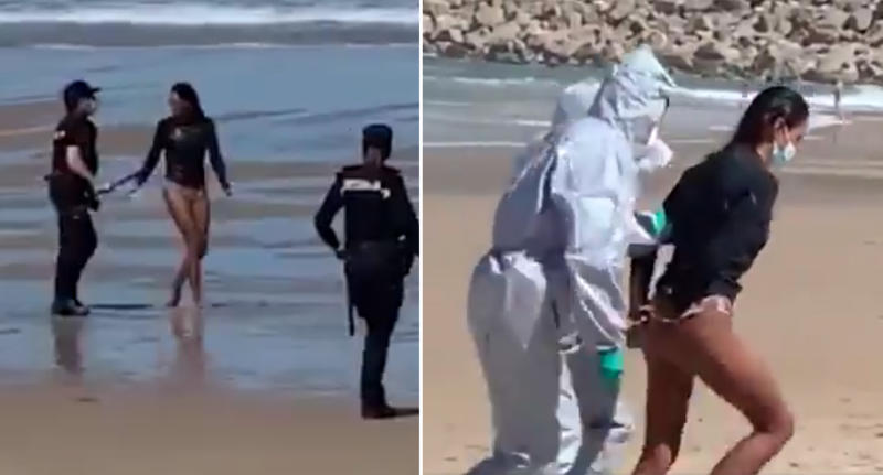 A woman is arrested on a beach in Spain by officers wearing white hazmat suits.