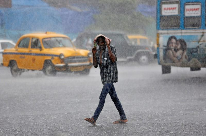 FILE PHOTO: A man covers his head as he crosses a road during heavy rain in Kolkata