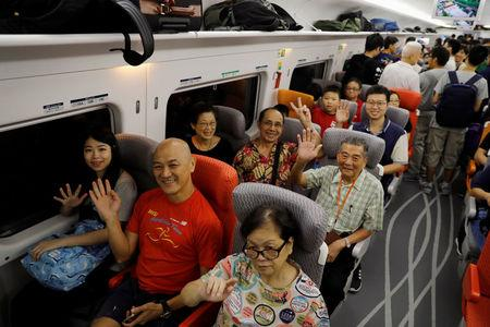 Passengers react on a first train departing from Hong Kong during the first day of service of the Hong Kong Section of the Guangzhou-Shenzhen-Hong Kong Express Rail Link, in Hong Kong