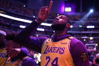 Los Angeles Lakers' LeBron James, wearing a No. 24 jersey, points up while shedding tears after the national anthem before the team's NBA basketball game against the Portland Trail Blazers in Los Angeles, Friday, Jan. 31, 2020. (AP Photo/Kelvin Kuo)
