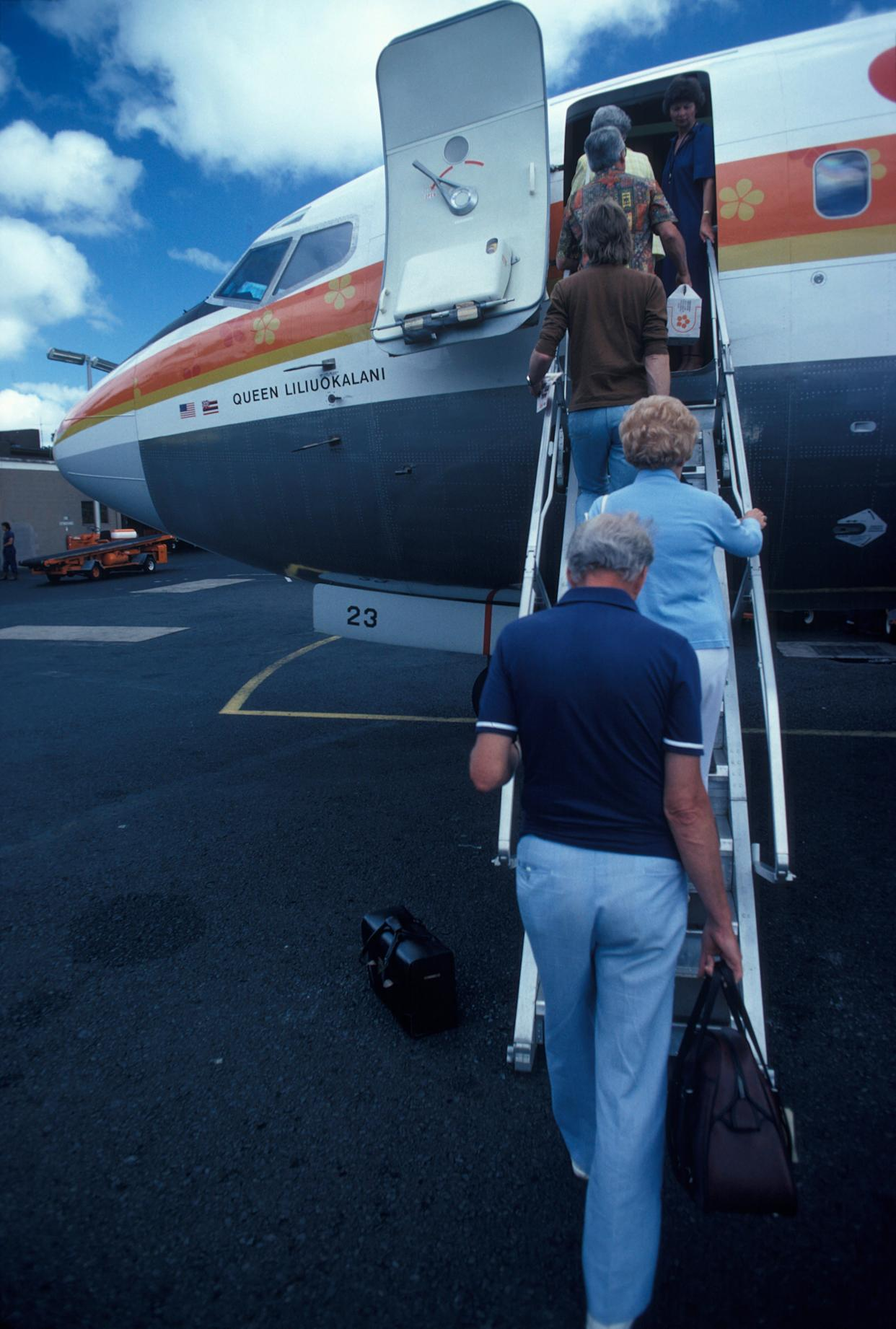 Passengers board an Aloha Airlines plane named after Hawaiian monarch 'Queen Liliuokalani' at Honolulu airport in Honolulu, Hawaii on Jan. 2, 1980.