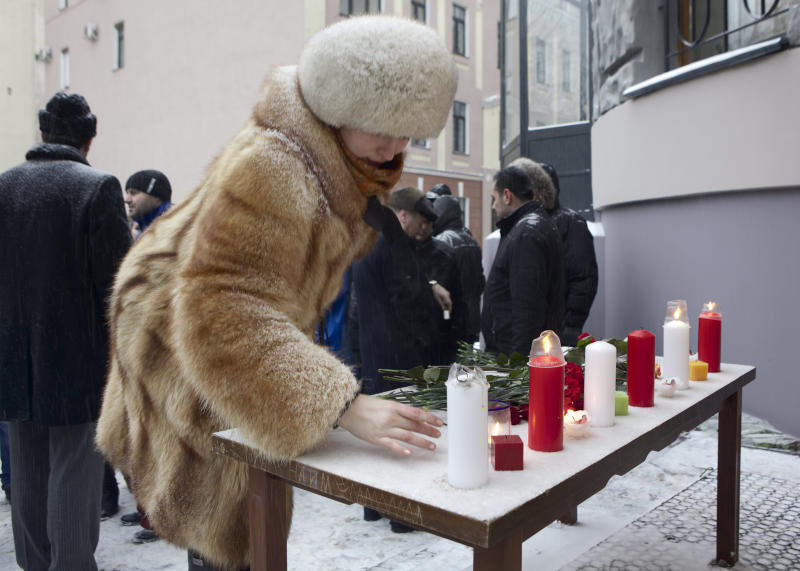 People light candles and lay flowers at the Syrian Embassy in Moscow, Thursday, Jan. 17, 2013. Pro-government Syrians and their Russian supporters gathered at the Syrian Embassy in memory of dozens of the Aleppo University's students who died during a terrorist attack. (AP Photo/Misha Japaridze)
