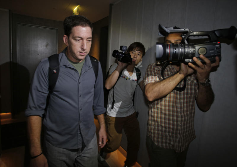 Glenn Greenwald, left, a reporter for The Guardian newspaper, walks out from his hotel room in Hong Kong Monday, June 10, 2013. Greenwald reported a 29-year-old contractor who claims to have worked at the National Security Agency and the CIA allowed himself to be revealed Sunday as the source of disclosures about the U.S. government's secret surveillance programs, risking prosecution by the U.S. government. (AP Photo/Vincent Yu)