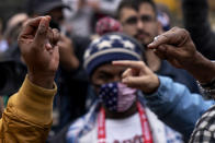 The hands of Biden supporter Angelo Austin, and Trump supporter C.L. Bryant, right, gesture as they argue while Trump supporters demonstrate against the election results outside the central counting board at the TCF Center in Detroit, Mich., Thursday, Nov. 5, 2020. (AP Photo/David Goldman)