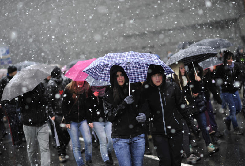Students march under the snow while they protest against austerity measures on  state schools, in Pamplona, northern Spain on Thursday, March 14, 2013. (AP Photo/Alvaro Barrientos)