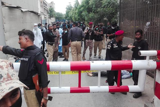 Policemen secure an area around a body outside the Pakistan Stock Exchange building after a group of gunmen attacked the building in Karachi on June 29, 2020. - A group of gunmen attacked the Pakistan Stock Exchange in Karachi on June 29, according to police and officials from the trading floor. (Photo by Asif HASSAN / AFP) (Photo by ASIF HASSAN/AFP via Getty Images)
