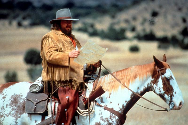 John Candy reads a map in a scene from the film 'Wagons East', 1994. (Photo by TriStar/Getty Images)