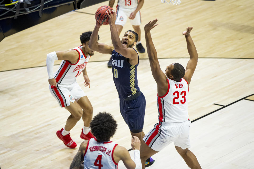 Oral Roberts' Kevin Obanor (0) goes up for a shot between Ohio State's Justice Sueing (14), Duane Washington Jr. (4) and Zed Key (23) during the first half of a first round game in the NCAA men's college basketball tournament, Friday, March 19, 2021, at Mackey Arena in West Lafayette, Ind. (AP Photo/Robert Franklin)