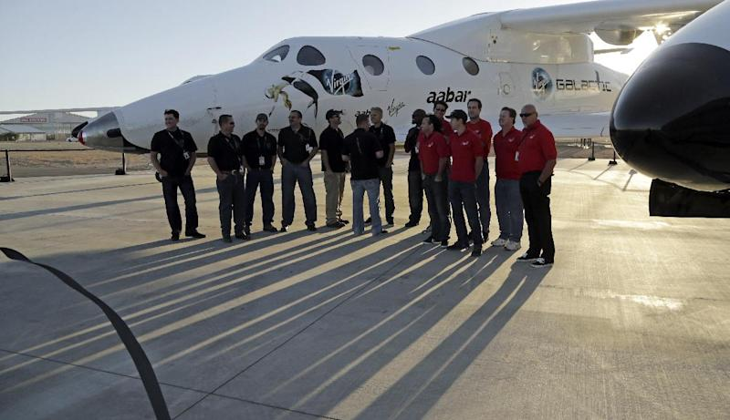 FILE- In this Wednesday, Sept. 25, 2013 file photo SpaceShipTwo is seen mounted under its mother ship White Knight with its support crew at a Virgin Galactic hangar at Mojave Air and Space Port in Mojave, California. One lucky citizen of the oil-rich United Arab Emirates could soon get the chance to be rocketed into space. Government-backed Aabar Investments on Sunday, April 20, 2014, announced the start of a competition to award an Emirati a free spot aboard Virgin Galactic's spaceship when it begins ferrying space tourists briefly into space. (AP Photo/Reed Saxon, File)