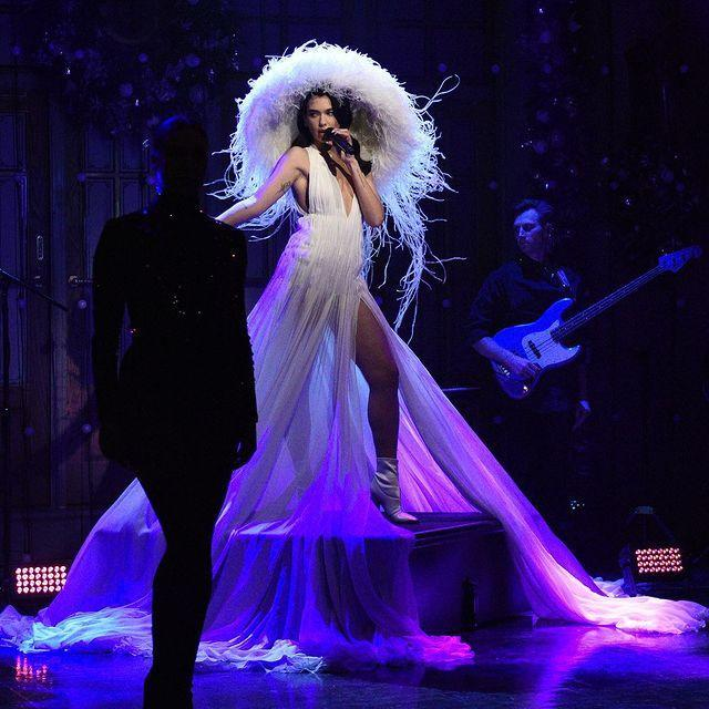 "<p>Dua Lipa was truly levitating in this dreamy couture moment for her musical performance on Saturday Night Live. The singer stunned in an ethereal ivory Valentino Haute Couture 2020 collection plissé gown, paired with a matching <a href=""https://www.dazeddigital.com/tag/philip-treacy"" rel=""nofollow noopener"" target=""_blank"" data-ylk=""slk:Phillip Treacy"" class=""link rapid-noclick-resp"">Phillip Treacy</a> for Valentino white oversized feathery hat and finished off with white pointed leather boots. </p><p><a class=""link rapid-noclick-resp"" href=""https://go.redirectingat.com?id=127X1599956&url=https%3A%2F%2Fwww.net-a-porter.com%2Fen-gb%2Fshop%2Fdesigner%2Fvalentino&sref=https%3A%2F%2Fwww.elle.com%2Fuk%2Ffashion%2Fcelebrity-style%2Fg19613955%2Fdua-lipas-style-file%2F"" rel=""nofollow noopener"" target=""_blank"" data-ylk=""slk:SHOP VALENTINO NOW"">SHOP VALENTINO NOW</a></p><p><a href=""https://www.instagram.com/p/CJCCA-wr7hY/?utm_source=ig_embed&utm_campaign=loading"" rel=""nofollow noopener"" target=""_blank"" data-ylk=""slk:See the original post on Instagram"" class=""link rapid-noclick-resp"">See the original post on Instagram</a></p>"