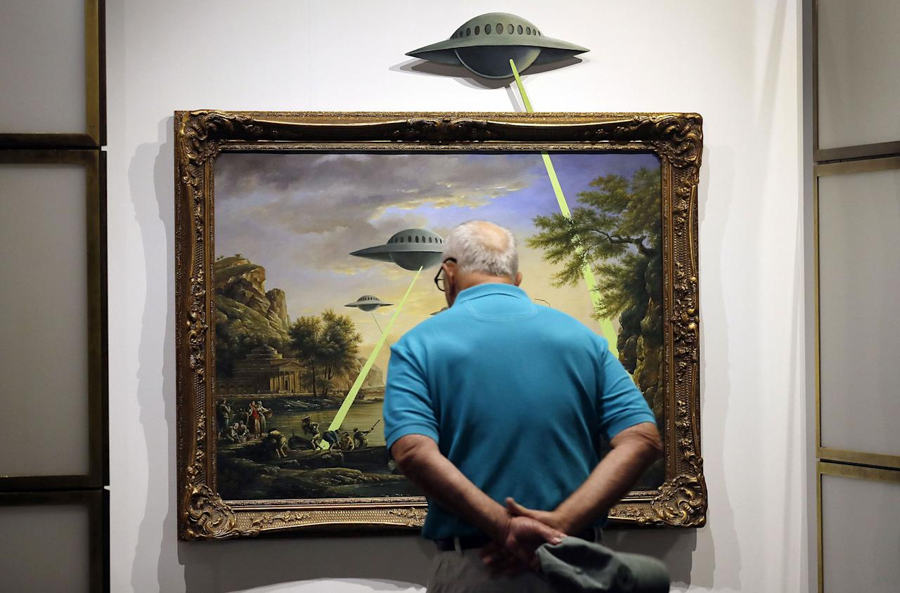 <p>A visitor examines the painting entitled 'UFO' by British Banksy is on display at the exhibition 'The Art of Banksy' in Berlin, Germany on June 20, 2017. (Felipe Trueba/EPA/REX/Shutterstock) </p>