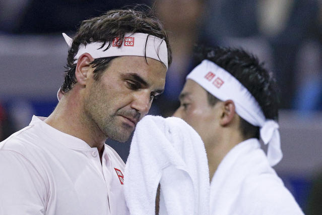 Roger Federer of Switzerland, left, and Kei Nishikori of Japan wipe faces during their men's singles quarterfinals match in the Shanghai Masters tennis tournament at Qizhong Forest Sports City Tennis Center in Shanghai, China, Friday, Oct. 12, 2018. (AP Photo/Andy Wong)