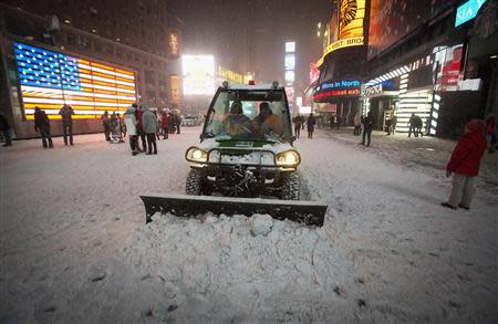 A snow plow pushes snow through Times Square in New York, January 3, 2014. REUTERS/Carlo Allegri