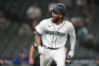 Seattle Mariners' J.P. Crawford turns toward the team dugout and lets out a yell as he begins to round the bases on his solo home run against the Texas Rangers during the seventh inning of a baseball game Saturday, May 29, 2021, in Seattle. (AP Photo/Elaine Thompson)