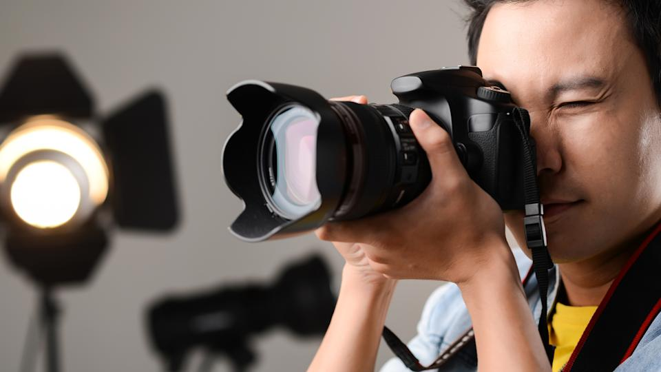 person looking into digital camera taking a photo in an indoor studio