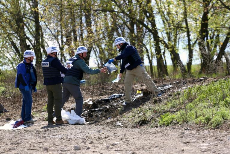 OSCE monitors inspect the site near the Ukrainian village of Pryshyb, near Lugansk, on April 25, 2017, where an OSCE patrol vehicle was destroyed by an explosion on April 23