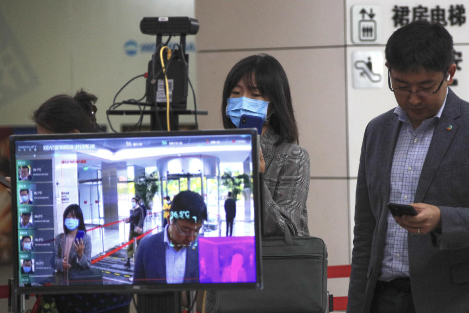 A monitor shows the temperature of people as they use their smartphones to scan their health code to help curb the spread of the coronavirus while entering an office building in Beijing, Thursday, Oct. 15, 2020. (AP Photo/Andy Wong)