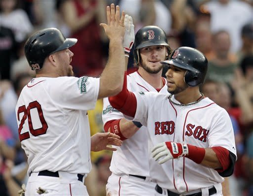 Boston Red Sox's Mike Aviles is congratulated at the plate by Kevin Youkilis (20) and Jarrod Saltalamacchia, who scored on his three-run home run in the second inning of an interleague baseball game against the Miami Marlins at Fenway Park in Boston on Wednesday, June 20, 2012. (AP Photo/Elise Amendola)